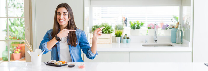 Wide angle picture of beautiful young woman eating delivery sushi smiling and looking at the camera pointing with two hands and fingers to the side.