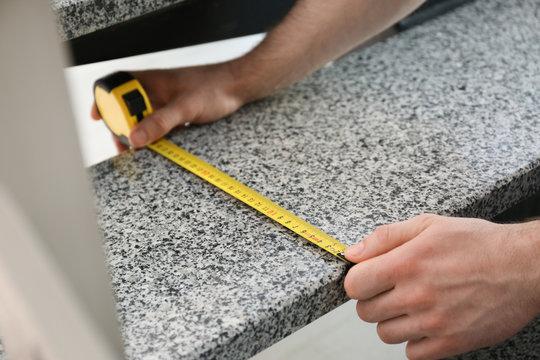 Man measuring stone step, closeup. Construction tool