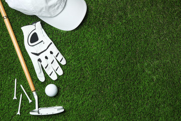 Flat lay composition with golf equipment on artificial grass, space for text