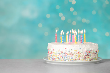 Birthday cake with burning candles on table against light blue background. Space for text Wall mural
