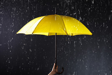 Woman holding bright umbrella under rain on dark background, closeup Wall mural