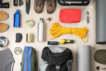 Flat lay composition with different camping equipment on wooden background Fototapete