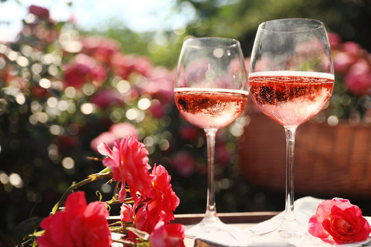 Glasses of rose wine on table in blooming garden, space for text