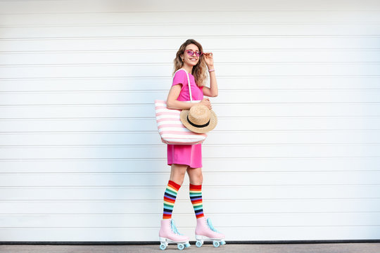 Happy young woman with retro roller skates near white garage door