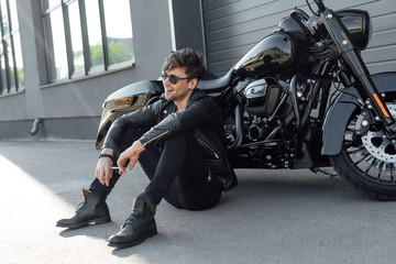 young man sitting near black motorcycle and holding cigarette Wall mural