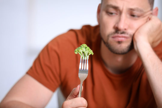 Unhappy man with broccoli on fork against light background, closeup