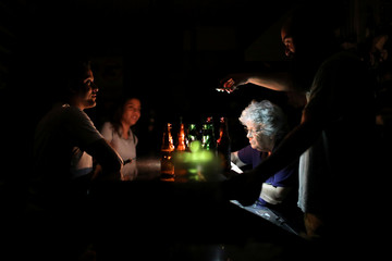 A man uses a cellphone to illuminate a vendor in  a bar during a blackout in Caracas