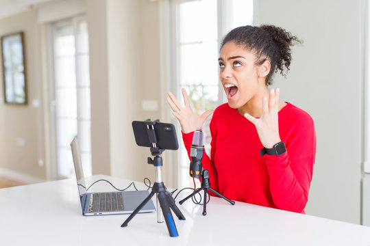 Young african american woman doing video call using smartphone camera and microphone crazy and mad shouting and yelling with aggressive expression and arms raised. Frustration concept.