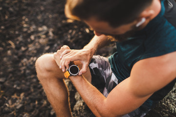 Young athletic man using fitness tracker or smart watch before run training outdoors. Close-up photo with dark background.