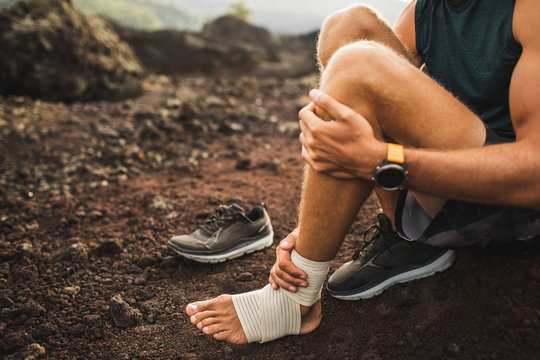 Man bandaging injured ankle. Injury leg while running outdoors. First aid for sprained ligament or tendon. Close-up on dark background.