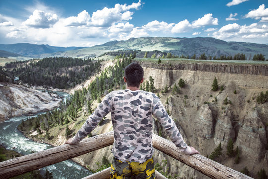 Tourist man enjoy the mountain river canyon view during his travel vacation to Yellowstone National Park