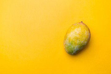 Fresh mango over yellow background or wallpaper, top view with copy space