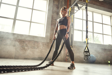 CrossFit training. Young athletic woman with perfect body doing crossfit exercises with a rope in the gym.