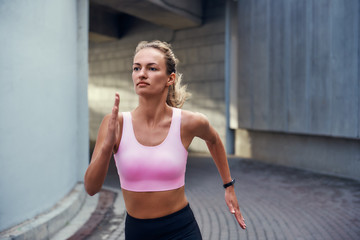 Morning cardio. Young woman in comfortable sports clothing is running outdoors along the street