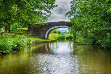 View of a British canal in rural setting with stone bridge