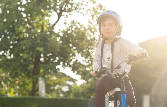 Smiling boy in safety helmet riding his bike.asian child on a bicycle at asphalt road in summer. Bike in the park