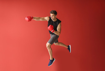 Sporty male boxer on color background