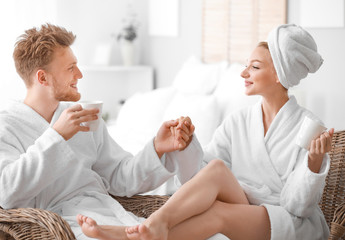 Wall Mural - Morning of happy young couple in bathrobes at home