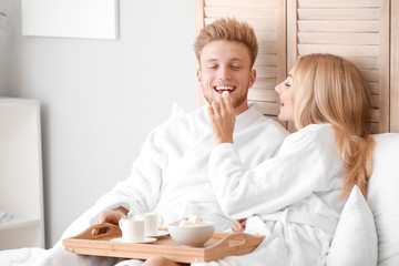 Wall Mural - Morning of happy young couple having breakfast in bed