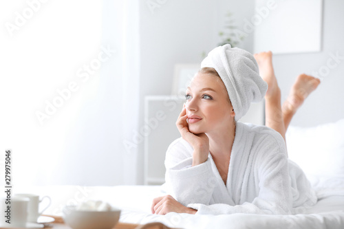 Wall mural Morning of young woman in bathrobe lying on bed