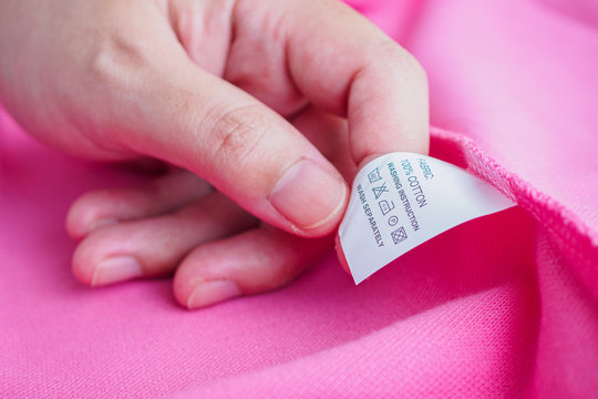Woman reading on laundry care washing instructions clothes label on pink cotton shirt