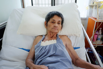 Asian elderly woman lay sick on bed.