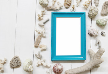 Blue Wooden photo frame on a white wood floor and have Shells and coral reefs.