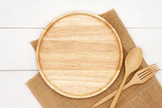 Empty round wooden plate with spoon, fork and rustic brown burlap cloth on white wooden table. Top view image.