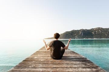 Person sitzt auf einem Steg und meditiert umgeben vom Meer beim Sonnenaufgang