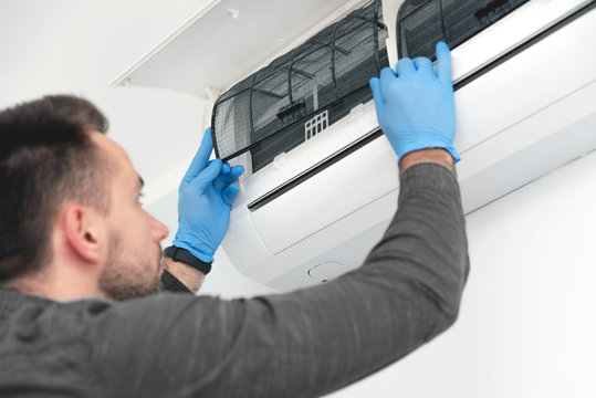Technician replacing filter in air conditioner