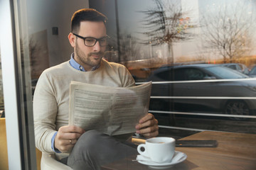 Man reading newspapers and drinking coffee