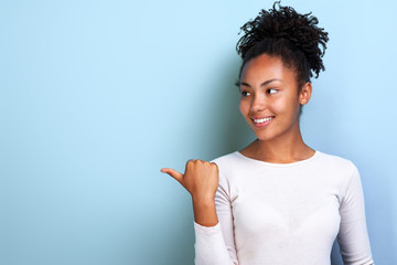 Attractive young woman pointing by her finger sideways place for copy space