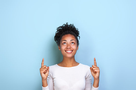 Attractive woman pointing by her both index fingers up to place for copy space