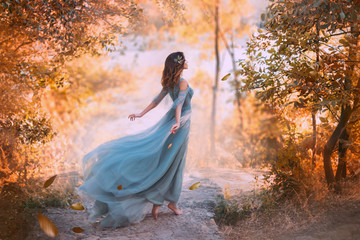 Fotorolgordijn Bestsellers Kids delightful light girl in sky blue turquoise dress with long flying train, princess of wind and daughter of storm, lady with dark hair throws fallen leaves to ground, autumn story in art processing.