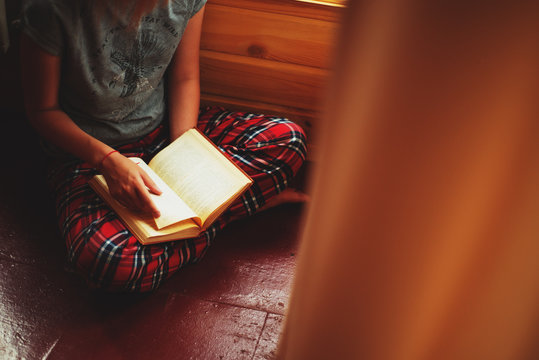 a girl in plaid pants reading a book on the floor by the window