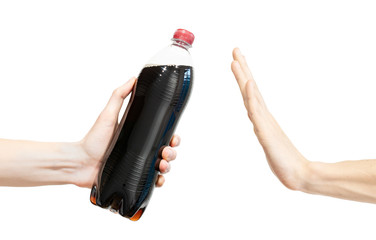 Say no black soda. Man says no to soda. Hand gesture to reject proposal to drink soda. Hand holding a bottle of cola to gives and another hand rejects on a white background. Refuse, ban, rejection