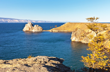 Lake Baikal autumn sunny day. The coast of Olkhon Island and the main natural sight is the Shamanka Rock and on the background of the Small Sea Strait. Autumn travel around the island
