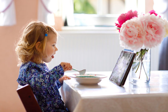 Adorable toddler girl eating healthy cereal with milk for breakfast and watching cartoons on tablet pc. Cute happy baby child in colorful clothes sitting in kitchen