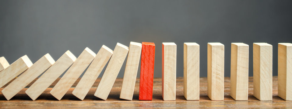 Wooden blocks and the effect of dominoes. Risk management concept. Successful strong business and problem solving. Reliable leader. Stop the destructive processes. Strategy development.