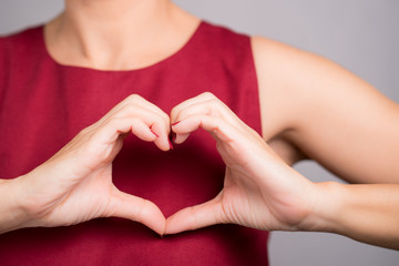 Closeup hands of a beautiful woman in stylish red outfit making heart shape gesture on her chest. Positive human emotion expression, Love, Caring, Body language, Health, Charity, Donation concept.