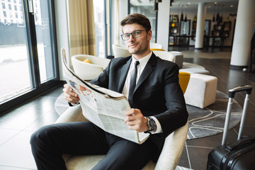 Portrait of pleased young businessman sitting on armchair and reading newspaper in hotel hall