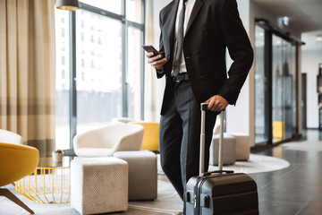 Cropped photo of confident businessman wearing suit holding smartphone and walking with suitcase in hotel lobby Wall mural