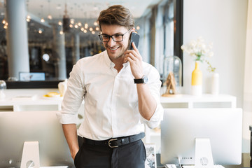 Image of attractive businesslike man talking on cellphone while working in office