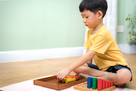 Portrait an asian little Montessori kid (3-6) learning about size, orders, sorting, arranging by engaged colorful wooden sensorial blocks. Educational toys, Cognitive skills, Left handed, Montessori