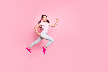 Full length side photo of beautiful little lady jumping high speed race champion dressed casual outfit isolated pink background