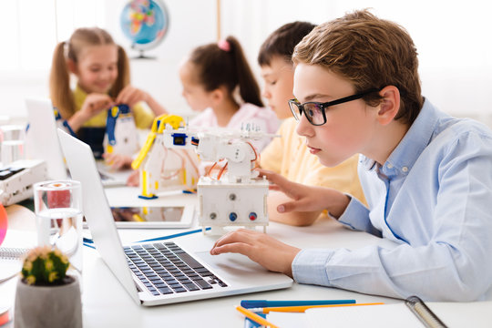 Boy using laptop, assembling robot in class