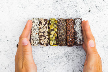 Chocolate energy protein bars with nuts, seeds, dry fruits. Healthy dietary snack. Vegan dessert. Woman hand hold sweet protein bar.