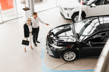 Family couple in dealership choose a car, man pointing to automobile. Top view
