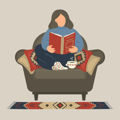Woman reading book on armchair at home.