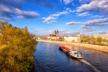 View of Magdeburg with cathedral, river Elbe and cargo boat, beautiful bright morning cityscape with blue sky and clouds, Saxony, Germany. Outdoor travel background